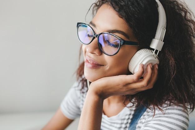 Fascinante Jeune Femme à La Peau Brune Et Aux Longs Cils Noirs Appréciant La Musique Préférée Dans De Grands écouteurs Photo gratuit