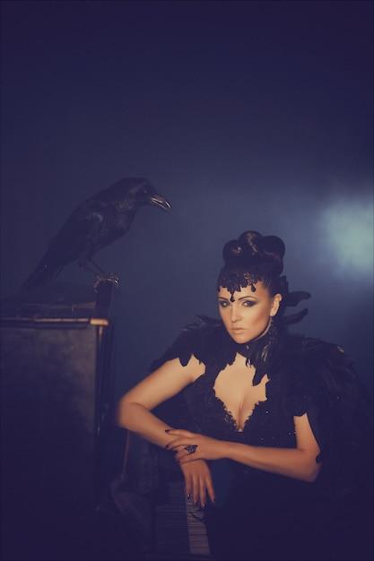 Fashion portrait gothique d'une belle brune avec le corbeau dans une longue robe noire faite de plumes de corbeau. halloween Photo Premium