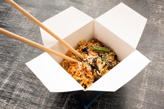 Fast-food asiatique avec des baguettes Photo gratuit