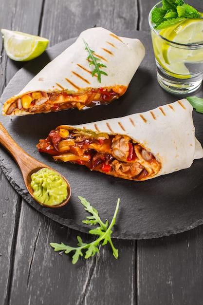 Fast food savoureux: burritos mexicains à la sauce guacamole sur fond en bois noir Photo Premium