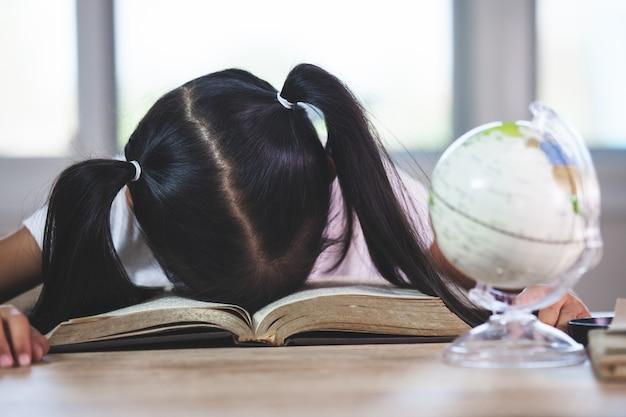 Fatigué asiatique petite fille endormie sur le livre ouvert dans la salle de classe Photo Premium