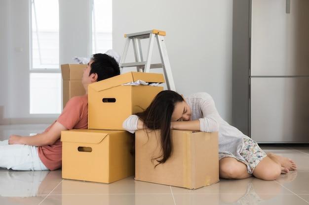 Fatigué couple asiatique dort au déménagement des boîtes Photo Premium