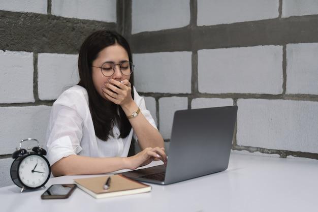 Fatigué, femme d'affaires somnolent à lunettes bâillant tout en utilisant un ordinateur portable pendant la nuit. Photo Premium