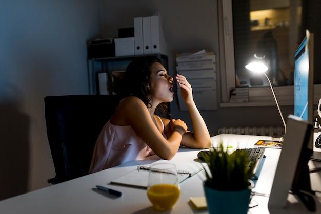 Fatigué femme endormie bâillant, travaillant au bureau, concept de surmenage et de privation de sommeil Photo Premium