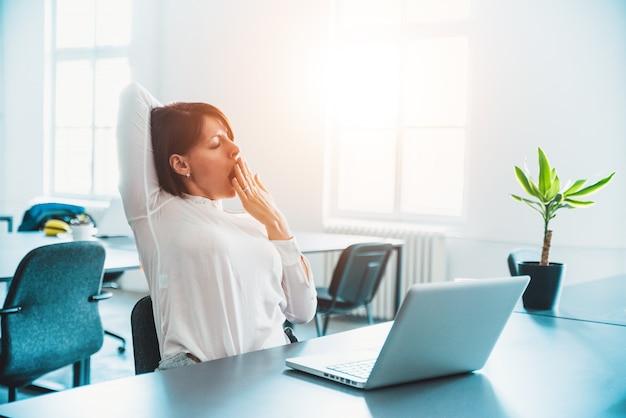 Fatigué, femme endormie bâillant, travaillant au bureau. Photo Premium