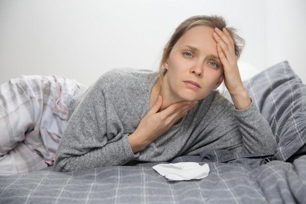 Fatigué Femme Malade Au Lit, Avoir Mal à La Gorge, Regardant La Caméra Photo gratuit