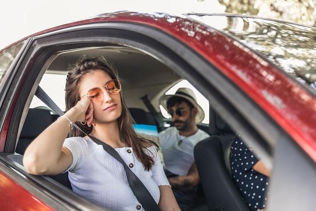 Fatigué de jeune femme dormant dans la voiture avec ses amis Photo gratuit
