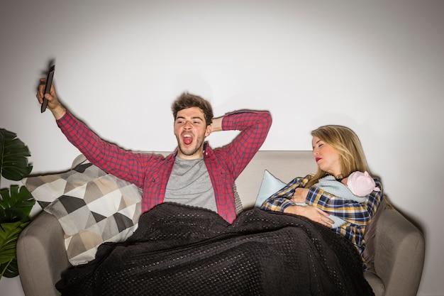 Fatigué père en regardant la télévision pendant que la mère avec bébé dort Photo gratuit