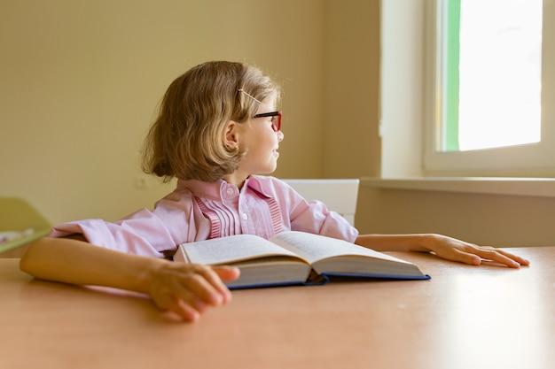 Fatigué petite étudiante regarde par la fenêtre alors qu'elle est assise à son bureau avec un gros livre Photo Premium