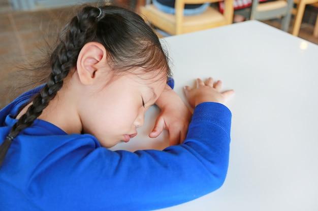 Fatigué de petite fille asiatique dort sur une table blanche au café. Photo Premium