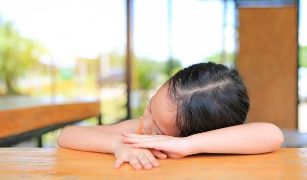Fatigué de petite fille asiatique qui dort sur la table en bois au café. Photo Premium