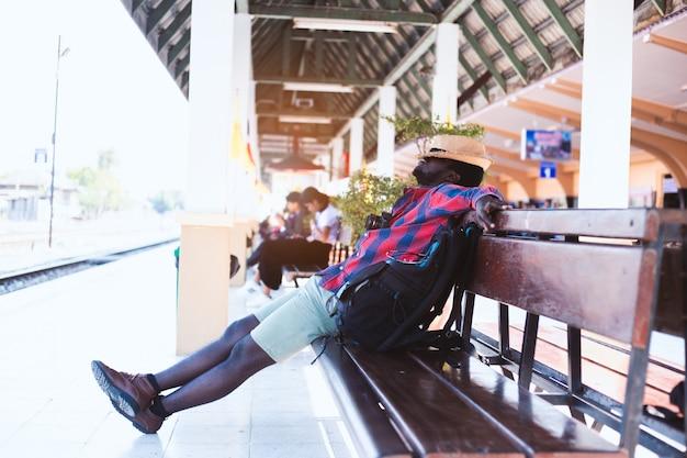 Fatigué voyageur africain dormant sur un banc à la gare Photo Premium