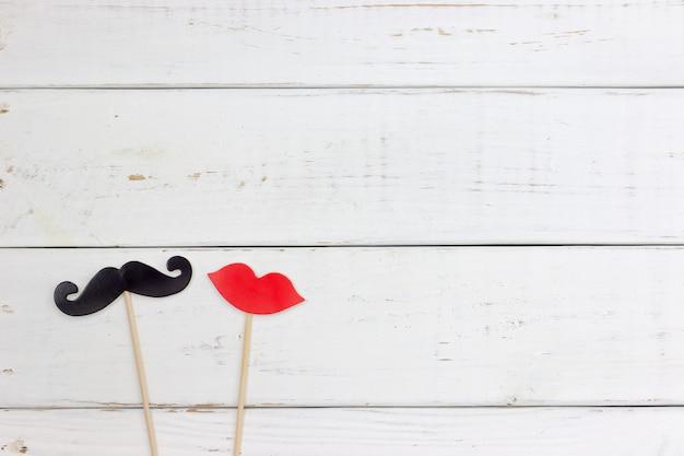 Fausse moustache et lèvre sur un fond en bois blanc en forme de cœur de papier. Photo Premium