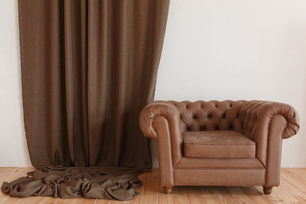 Fauteuil classique marron en textile à l'intérieur avec rideau et plancher en bois Photo gratuit