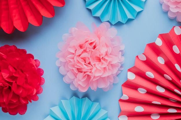 Faux belles fleurs en papier origami décoratif sur la surface bleue Photo gratuit