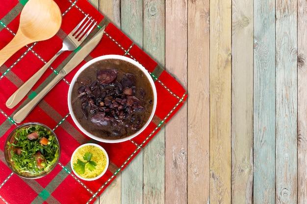 Feijoada brésilien. avec un fond en bois. vue de dessus - image Photo Premium