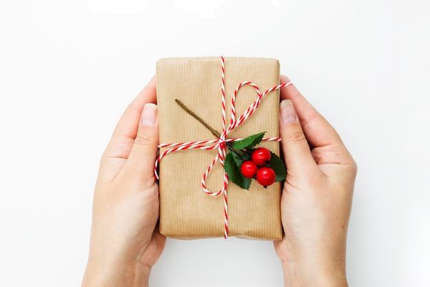Femal main tenant une boîte-cadeau, enveloppé dans du papier kraft isolé sur fond blanc. Photo Premium