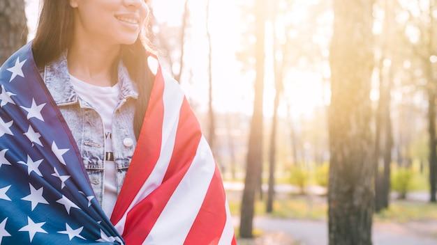 Femelle méconnaissable enveloppant dans le drapeau américain par une chaude journée d'été Photo gratuit