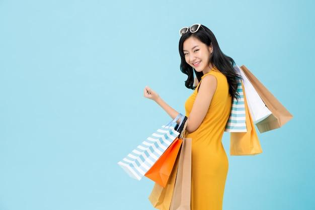 Femme accro du shopping asiatique portant des sacs colorés Photo Premium