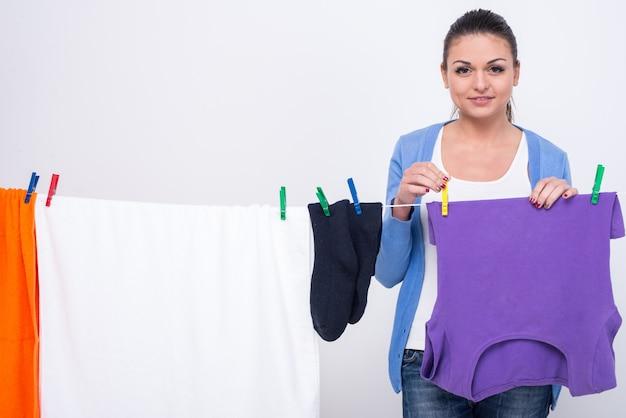 Femme accrochant des vêtements sur une corde à linge. Photo Premium