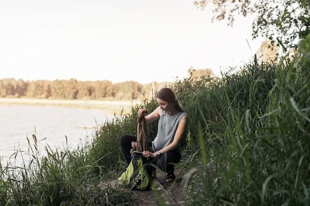 Femme accroupie près du lac retirant les vêtements du sac à dos Photo gratuit
