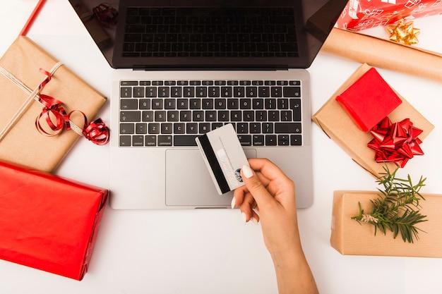 Femme achetant des cadeaux de noël en ligne avec des cadeaux sur la table Photo gratuit