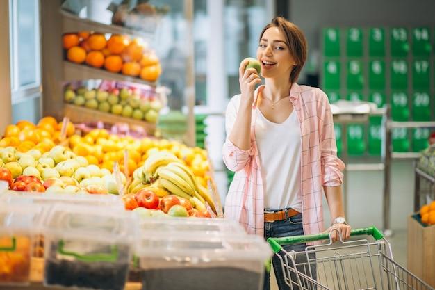 Femme achetant à l'épicerie Photo gratuit