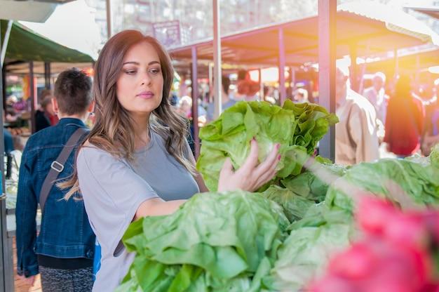Femme achetant des fruits et légumes au marché alimentaire local. marché avec une variété de légumes biologiques. portrait d'une belle jeune femme choisissant des légumes à feuilles vertes Photo gratuit
