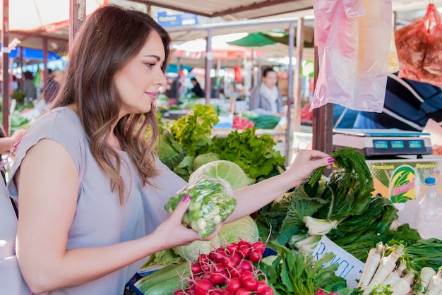 Femme achetant des légumes bio frais sur le marché de la rue. femme souriante aux légumes au marché. concept de shopping alimentaire sain Photo gratuit