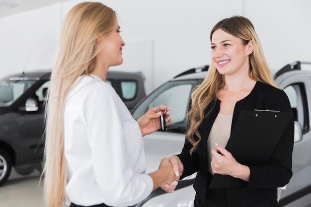 Femme achetant une nouvelle voiture chez un concessionnaire Photo gratuit
