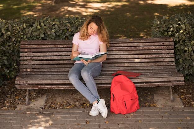 Femme adolescente attentive avec manuel sur banc Photo gratuit