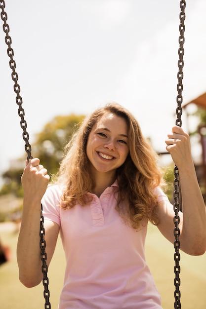 Femme Adolescente Joyeuse Sur Les Balançoires Photo gratuit