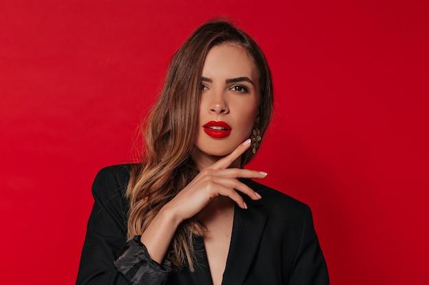 Femme Adorable Avec Maquillage De Soirée Posant Sur Un Mur Rouge, Touchant Son Visage Photo gratuit