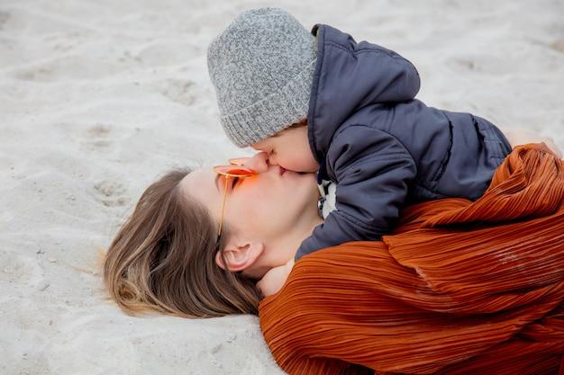Femme Adulte Avec Un Garçon Enfant En Bas âge, Couchée Sur Le Sable. Photo Premium
