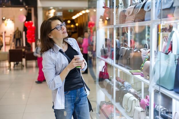 Femme Adulte En Regardant La Vitrine Avec Des Sacs Photo Premium