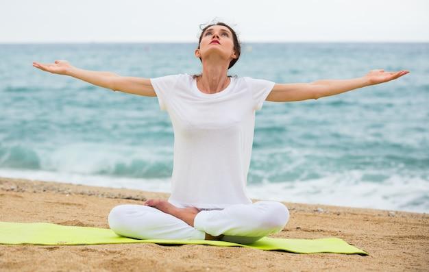 Femme adulte en t-shirt blanc est assis et pratique asana Photo gratuit