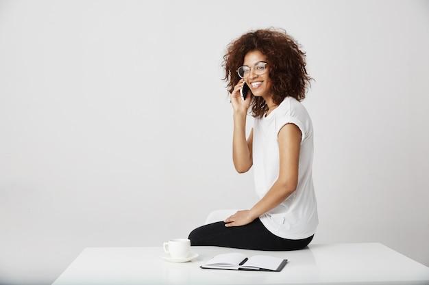 Femme D'affaires Africaine Riant Parlant Au Téléphone Sur Le Lieu De Travail, Ayant Un Appel De Son Manager Sur L'art Qu'elle Fait. Photo gratuit