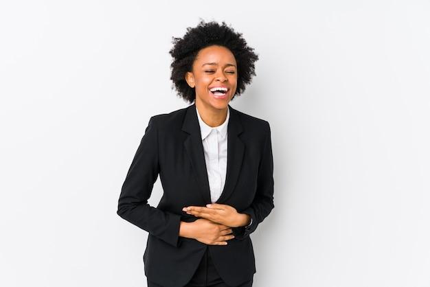 Femme D'affaires Afro-américaine D'âge Moyen Sur Un Fond Blanc Rit Joyeusement Et S'amuse à Garder Les Mains Sur Le Ventre. Photo Premium