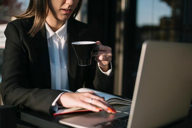 Femme d'affaires à l'aide d'un ordinateur portable tout en prenant une tasse de café Photo gratuit