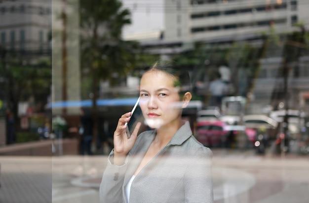 Femme d'affaires à l'aide d'un smartphone au verre de réflexion de l'immeuble de bureaux. Photo Premium