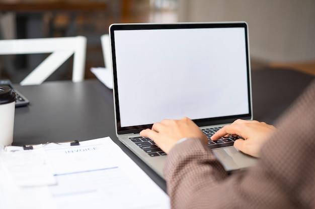 Femme d'affaires à l'aide et en tapant sur l'ordinateur portable écran blanc maquette à son bureau. Photo Premium