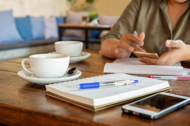 Femme d'affaires à l'aide de téléphone portable au café à la pause café. Photo Premium