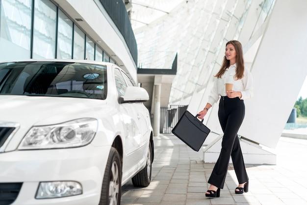 Femme d'affaires allant à la voiture Photo gratuit