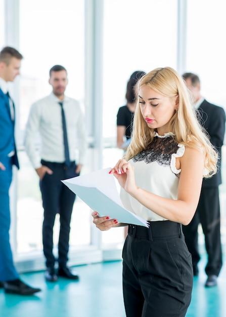 Femme d'affaires analysant des documents avec ses collègues en arrière-plan Photo gratuit