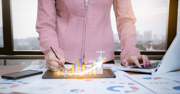 Femme d'affaires analysant des graphiques avec des réseaux sociaux de technologie informatique Photo Premium