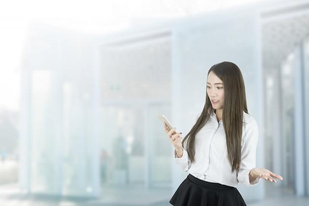 Femme d'affaires asiatique confuse à l'aide de smartphone. Photo Premium