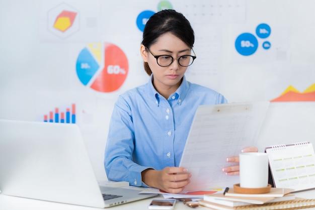 Femme d'affaires asiatique, faites attention tout en travaillant - concepts de business et finance. Photo Premium