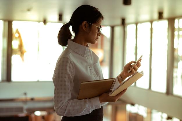 Femme d'affaires asiatique occupée porte des lunettes à l'aide d'un message texte lu tout en lisant un rapport financier Photo Premium