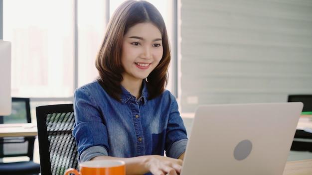 Femme d'affaires asiatique professionnelle travaillant à son bureau via un ordinateur portable. Photo gratuit
