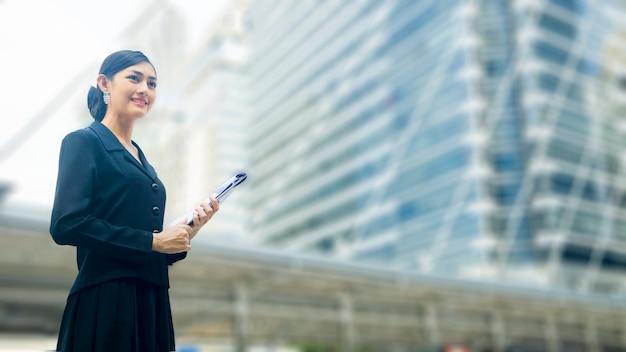 Femme d'affaires asiatique se dresse avec un dossier papier de présentation et de présentation confiant dans un espace public extérieur Photo Premium